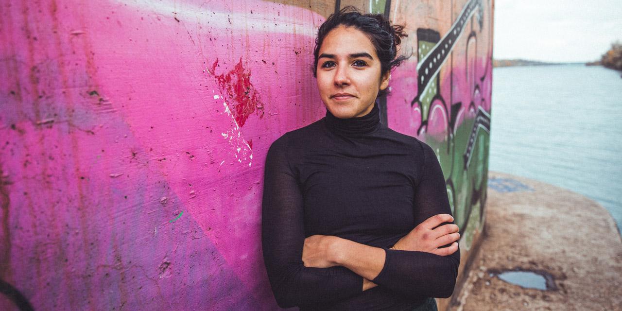 Sara Hassan lehnt an einer Betonwand