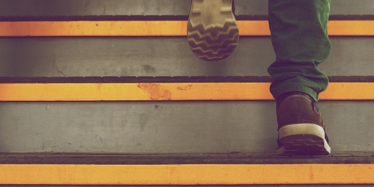 Füße, die eine Treppe hinaufsteigen
