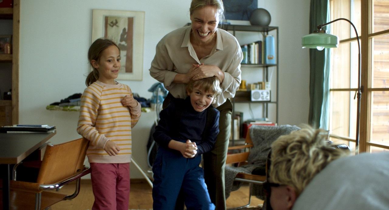 """Nina Hoss in einer Szene aus """"Schwesterlein"""" mit Kindern, alle lachen und schauen auf die Couch, wo der Bruder und Onkel im Film sitzt."""