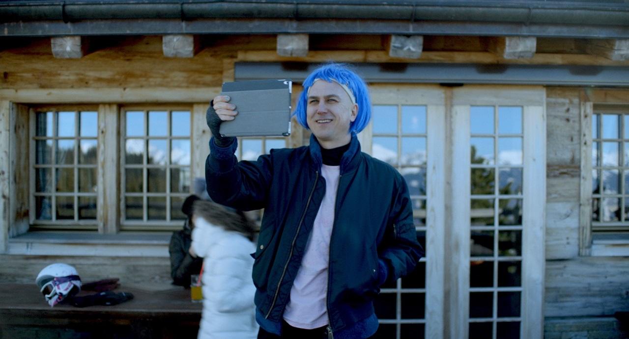 """Lars Eidinger spielt in """"Schwesterlein"""" einen an Leukämie erkrankten Schauspieler. Er trägt eine blaue Perücke, steht im Schnee auf Schweizer Bergen und fotografiert mit einem iPad."""