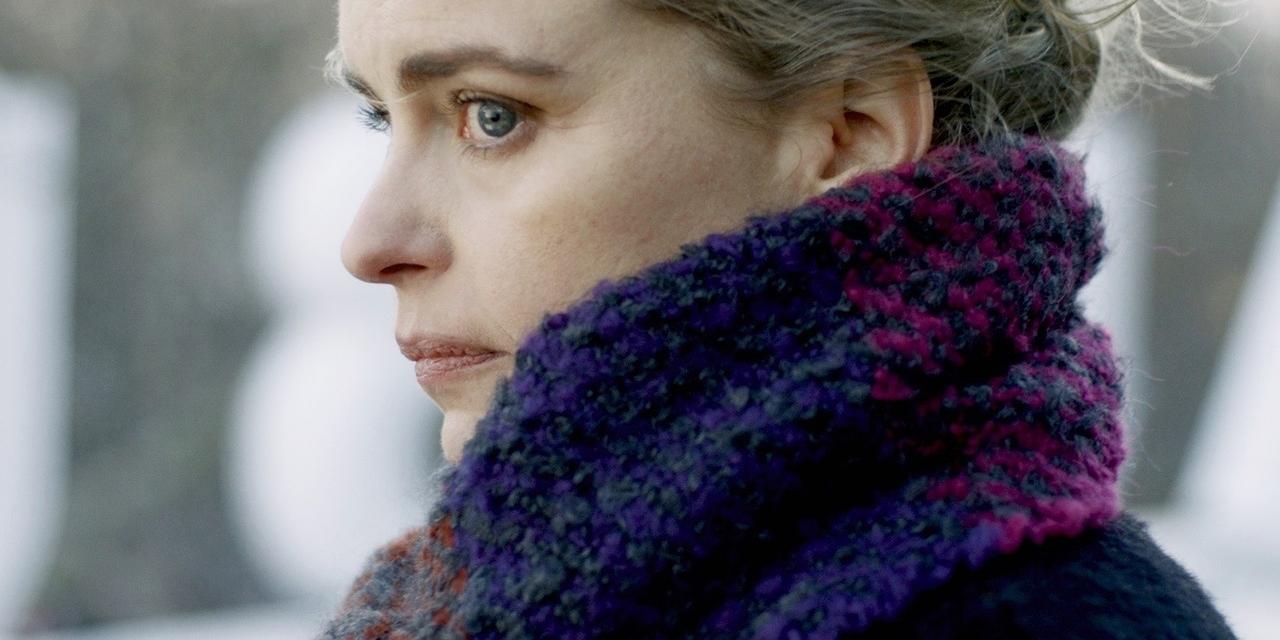 Nina Hoss trägt einen Schal und schaut.