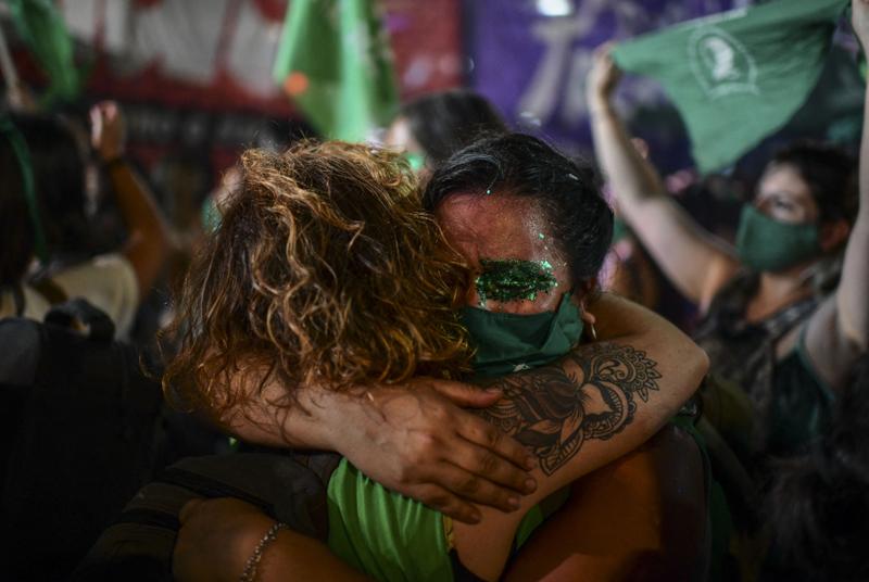 Zwei Frauen umarmen sich, sie sind in Grün gekleidet und geschminkt.
