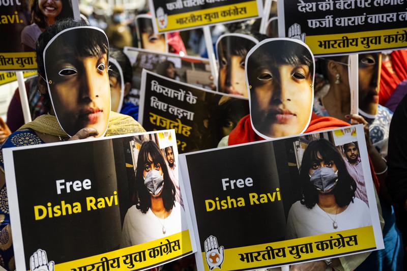 Protestierende fordern die Freilassung von Disha Ravi und tragen Masken mit einem Foto von ihr.