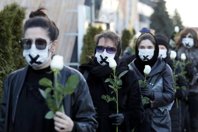 Demonstration in Belarus. Frauen tragen weißen Masken mit schwarzem Kreuz, in den Händen weiße Rosen.