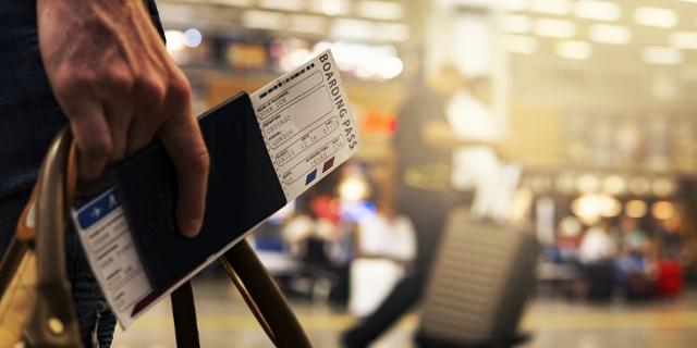 Reisepass und Boarding Pass in einer Hand gehalten