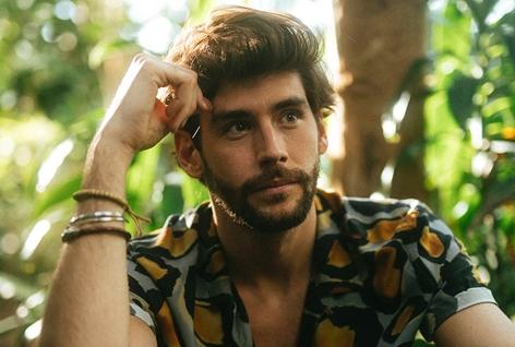 Sänger Alvaro Soler sitzt zwischen Bräumen und schaut verträumt zur Seite