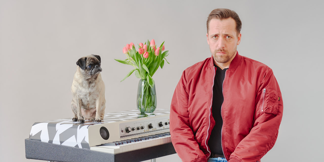 Danger Dan sitzt traurig neben dem Klavier, auf dem ein Mops sitzt und ein Strauß Tulpen steht