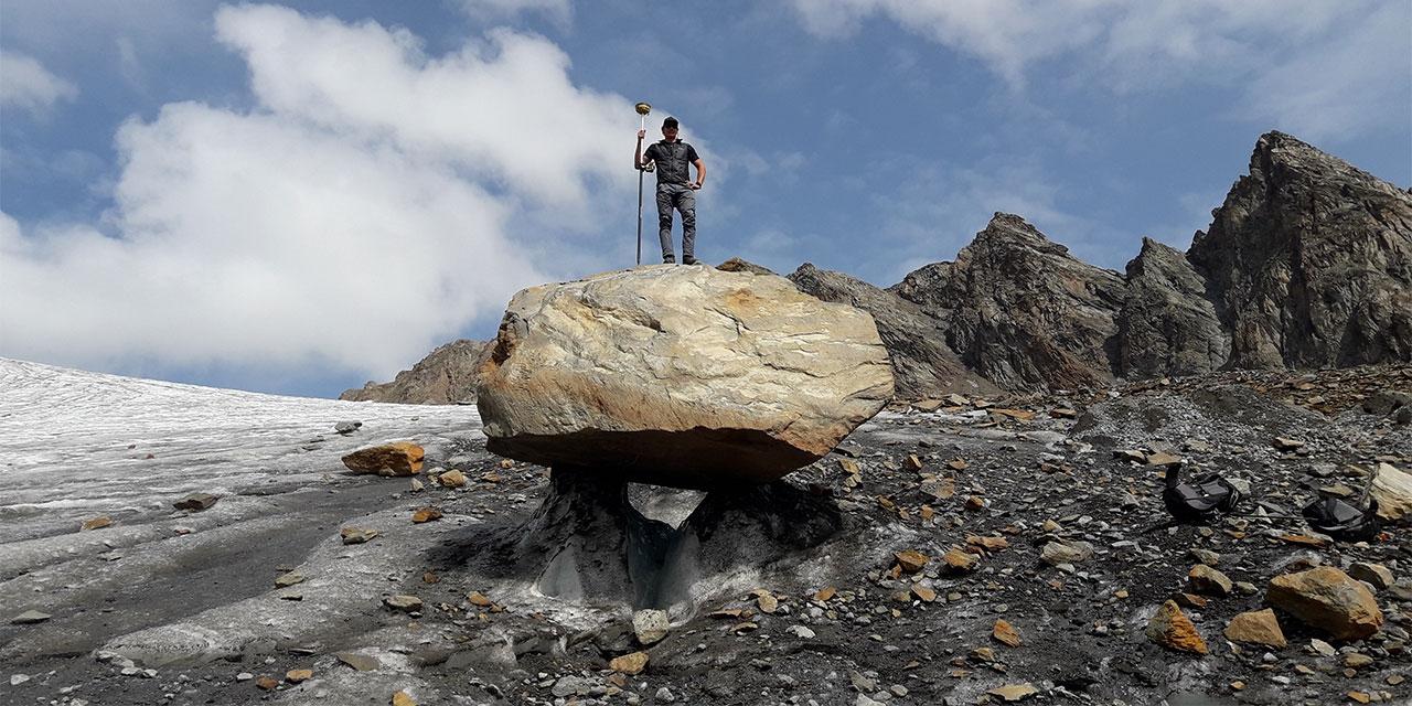 Gletschermesser bei der Arbeit mit Messinstrumenten auf einem Fels vor dem Gletscher