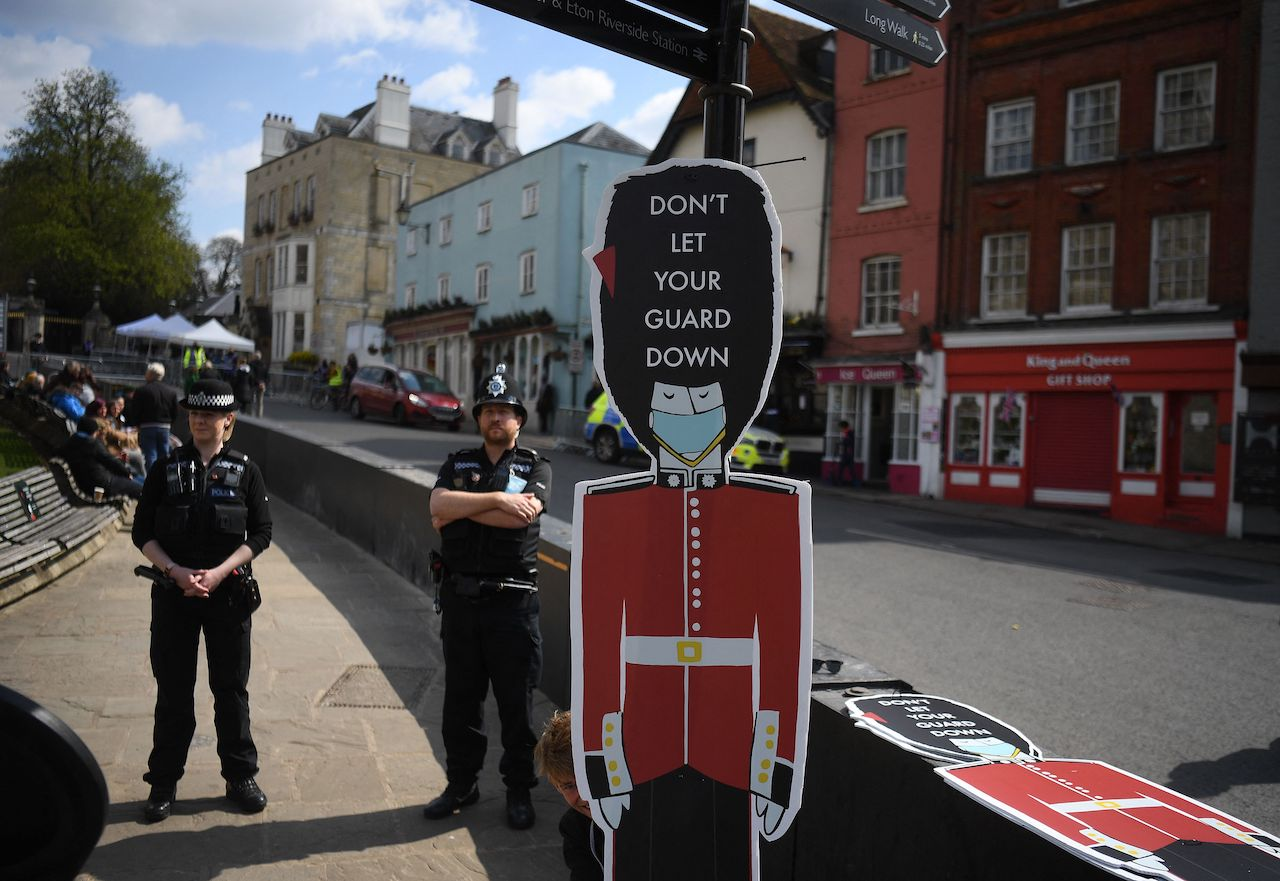 """A worker installs Covid-19 information signs depicting Coldstream Guards wearing face coverings, and the words """"Don't let your Guard down"""", outside Windsor Castle in Windsor"""