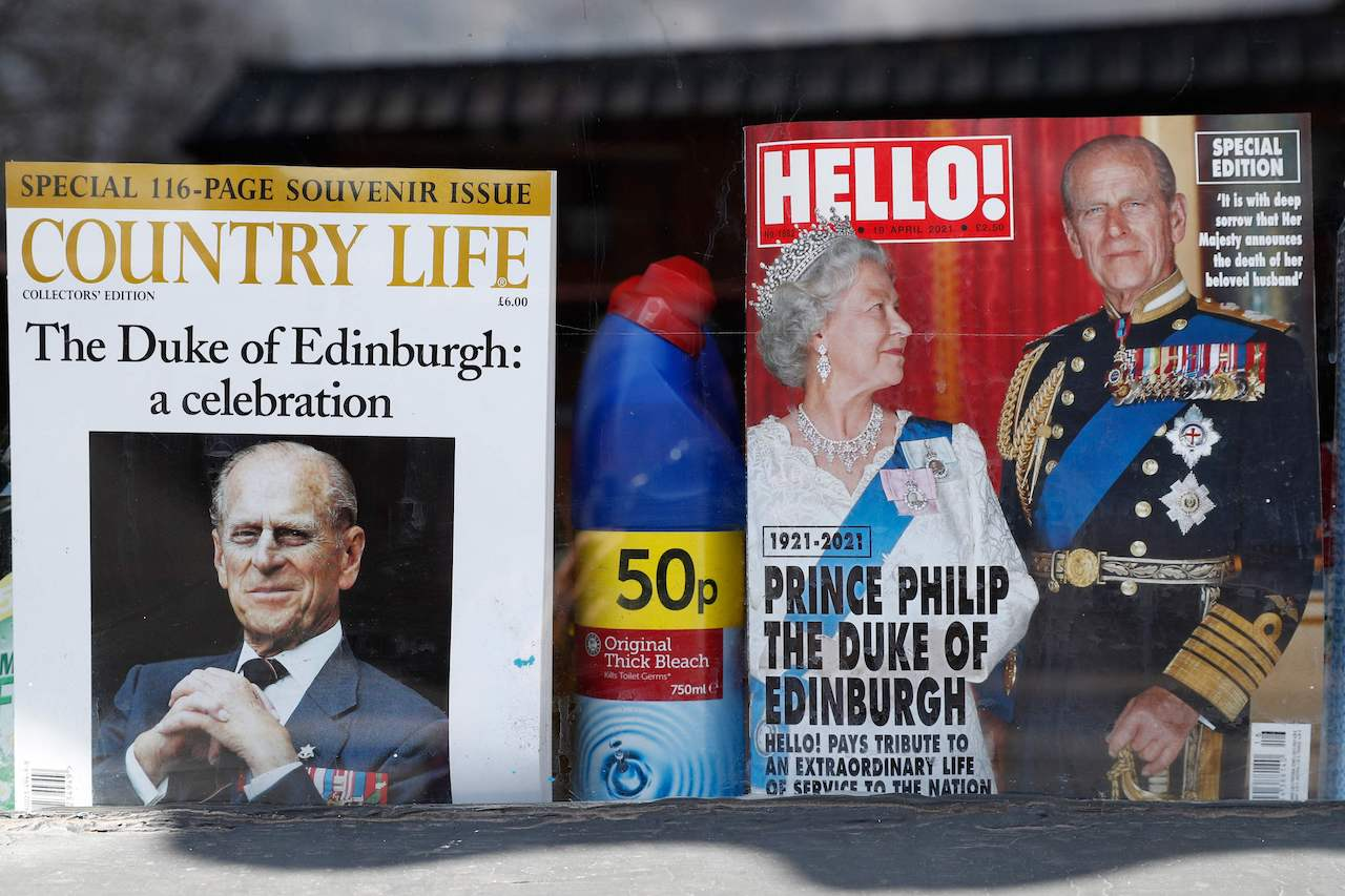 Magazines featuring Britain's Queen Elizabeth II and Britain's Prince Philip, Duke of Edinburgh are displayed in a shop window in Windsor