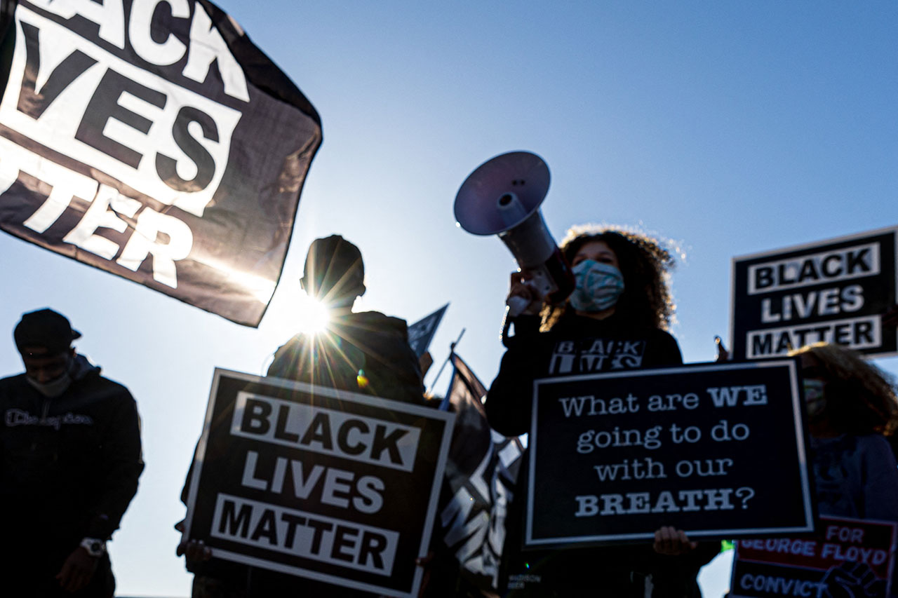 """Demonstrators hold """"Black Lives Matter"""" signs as they participate in the """"Justice for George Floyd"""" march outside the Minnesota State Capitol on March 19, 2021 in Saint Paul, Minnesota"""