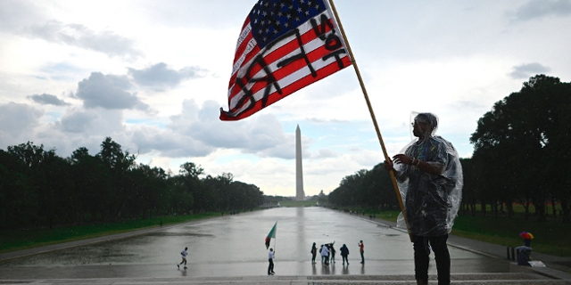 "A demonstrator waves an American flag with the words ""Not Free"" painted on it in front of the Washington Monument during a Juneteenth march and rally in Washington, DC, on June 19, 2020."
