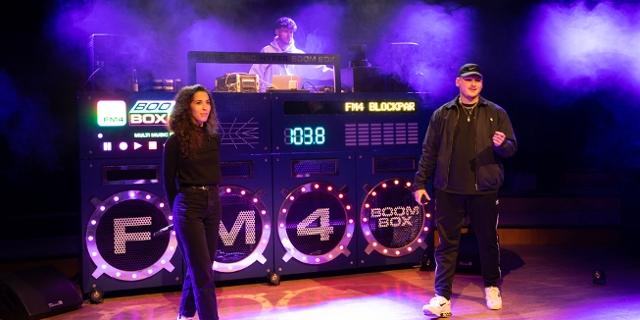 Slav auf der Bühne mit FM4 Moderatorin Lisa Schneider. Im Hintergrund die FM4 Boombox