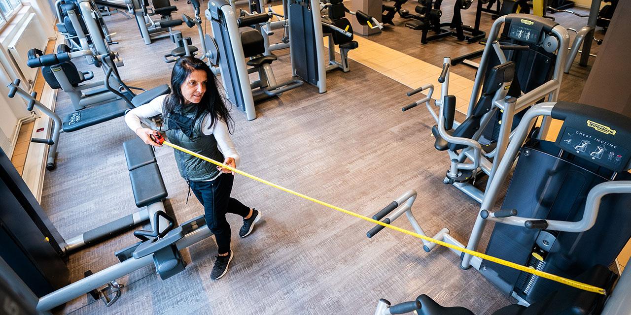 Eine Trainerin misst am Donnerstag, 28. Mai 2020, mit einem Massstab den Abstand zwischen Trainingsgeräten anl. letzter Vorbereitungen zur Wiedereröffnung eines Fitnesscenter in Wien