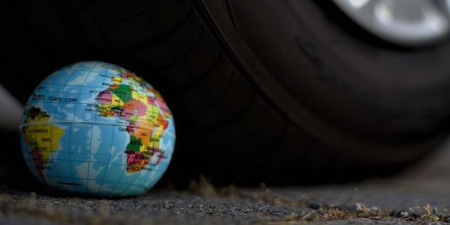 Symbolbild Klimawandel: Autorreifen zerdrückt eine kleine Erdkugel
