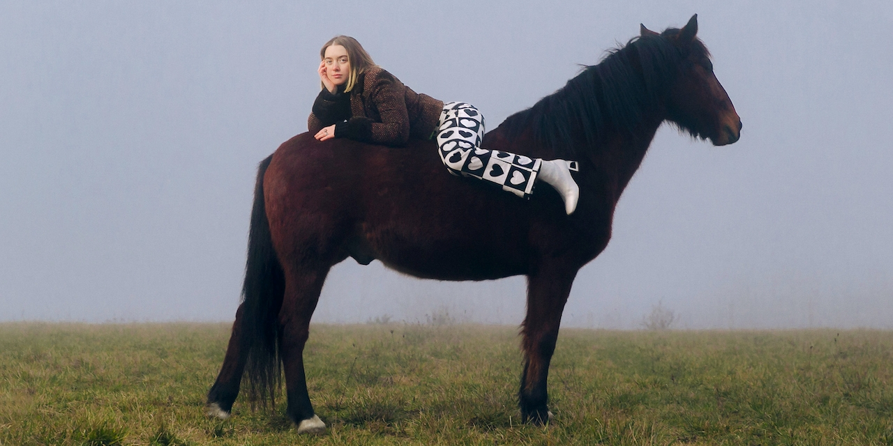 Florence Arman liegt auf dem Rücken eines Pferdes
