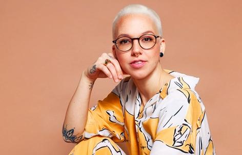 Sängerin Stefanie Heinzmann sitzend vor orangem Hintergrund
