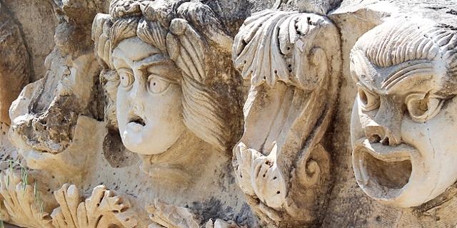 Gesichter aus Stein: eines lacht, eines weint