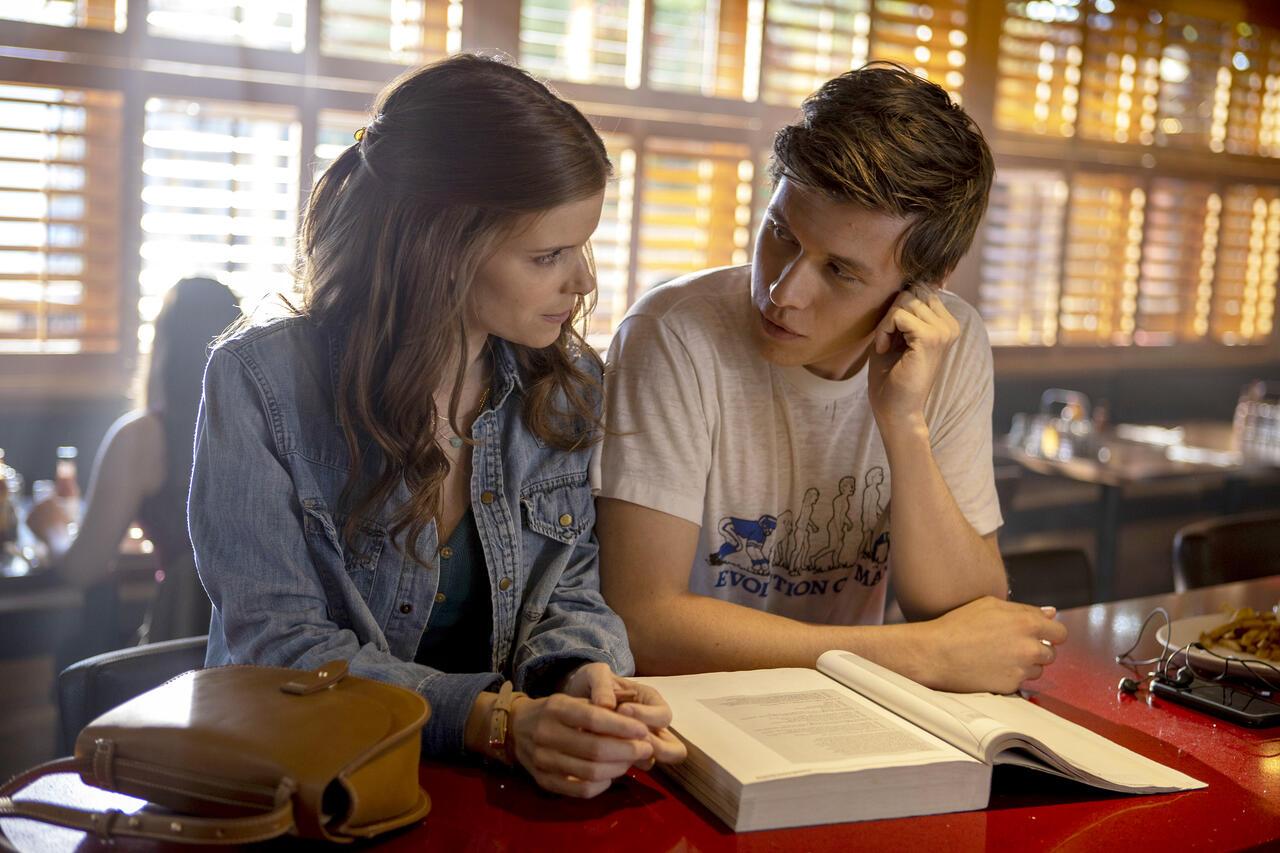 """Kate Mara und Nick Robinson setzen nebeneinander an einem Tresen in einem Lokal und schauen sich an. Szene aus der Serie """"A Teacher""""."""