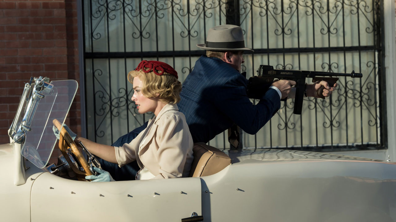 """Filmstill aus """"Dreamland"""": Gangsterpaar auf der Flucht, Frau am Steuer eines Autos, Mann zielt mit Maschinenpistole nach hinten"""