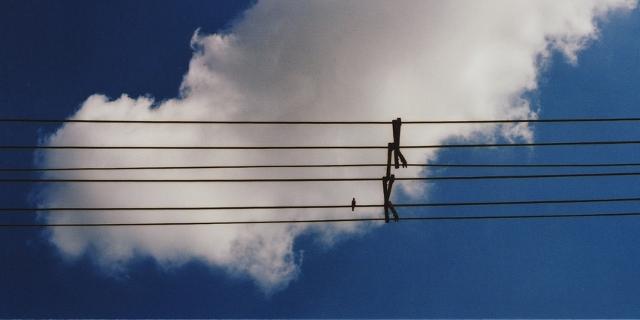 Kabel vor blauem Himmel mit weißer Wolke