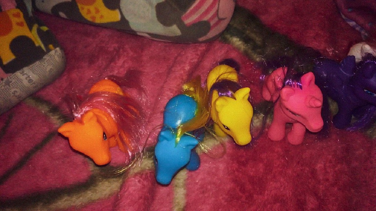 """My Little Pony Spielzeug auf einer Decke und eine Kinderhand. Filmstill aus """"I love you I miss you I hope I see you before I die""""."""
