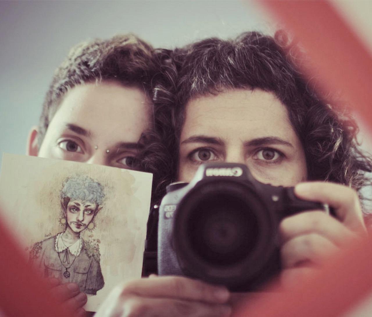 """Ein Teenager und eine Mutter schauen in einen Spiegel, der Teenager hält eine Zeichnung hoch, die Mutter die Kamera. Filmstill aus """"Treshold""""."""