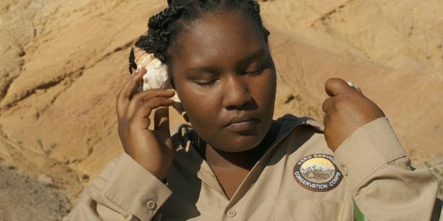 """Eine junge Schwarze hält eine Muschel an ihr Ohr. Filmstill aus """"Victoria""""."""