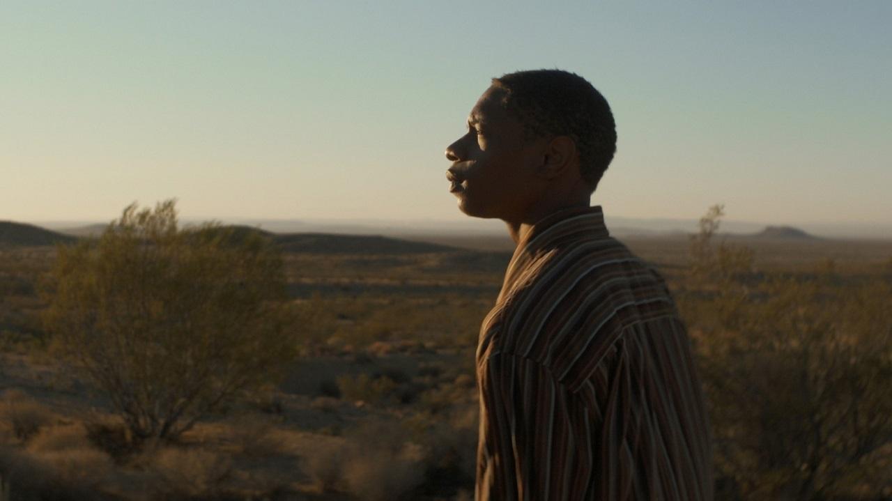"""Lashay Warren steht in der Wüste und blickt über das Land. Filmstill aus der Doku """"Victoria""""."""