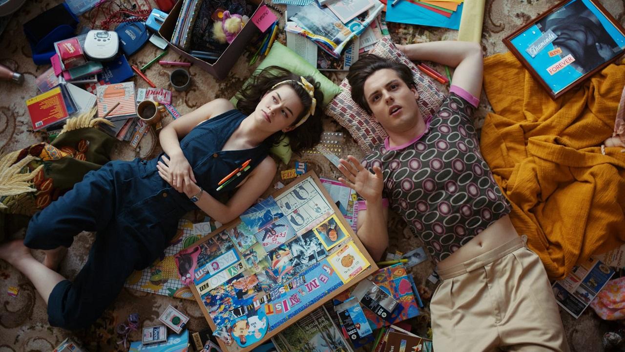 """Naomi Higgins und Wil King liegen als Peggy und Austin in der Serie """"Why Are You Like This"""" inmitten lauter Sachen auf dem Boden."""