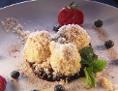 Schwarzbeerknöderl mit gerösteten Kokosflocken auf warmem Fruchtspiegel