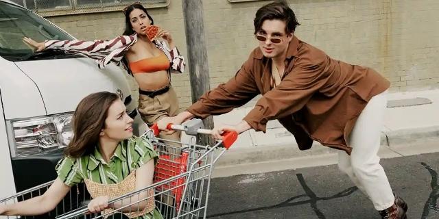 """Naomi Higgins sitzt in einem Einkaufswagen, den Wil King schiebt und Olivia Junkeer isst eine Pizzaschnitte. Alle drei spielen in der Serie """"Why Are You Like This""""."""