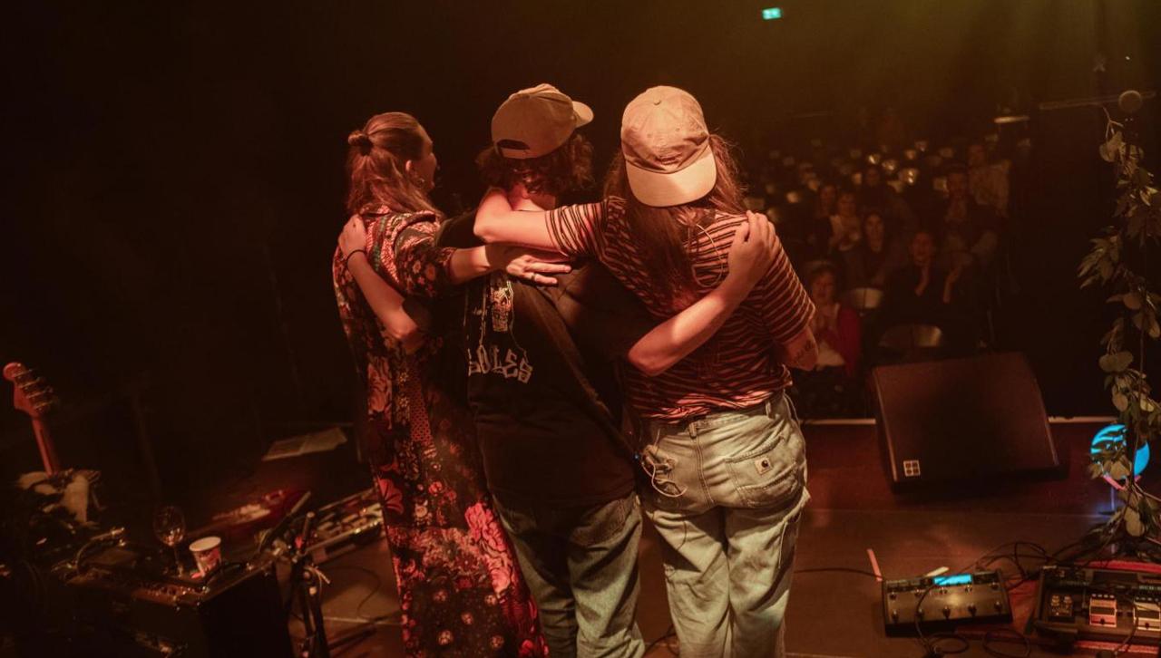 Band auf der Bühne, Publikum sitzt mit Abständen auf Sesseln