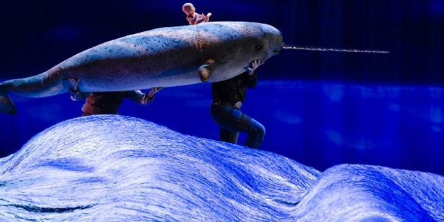 Theaterszene: Ein Narwal wird von zwei Personen über das Meer getragen, auf ihm sitzt eine Babypuppe