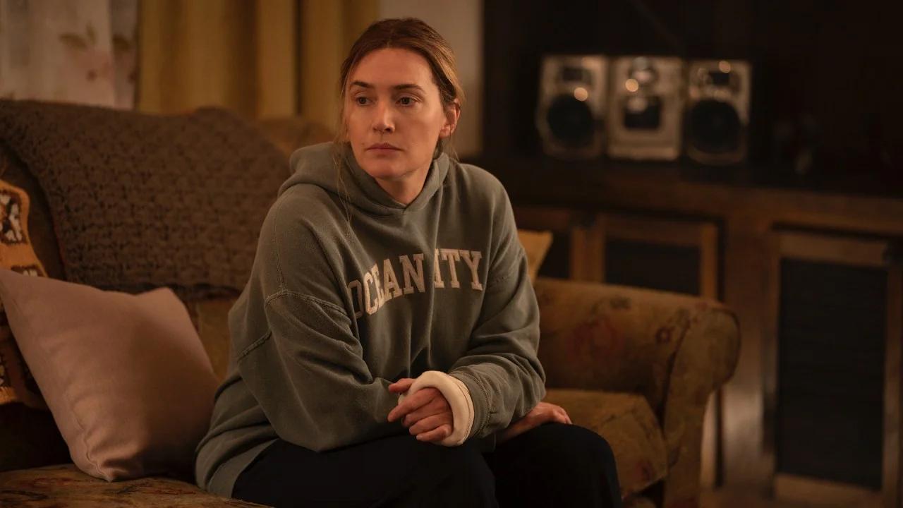 Eine Frau mit Gips am linken Arm sitzt auf einem Sofa