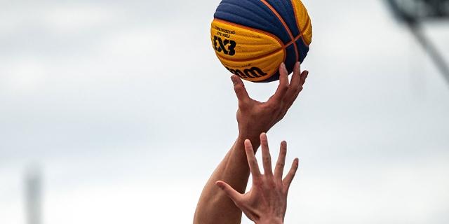Zwei Hände an einem Basketball