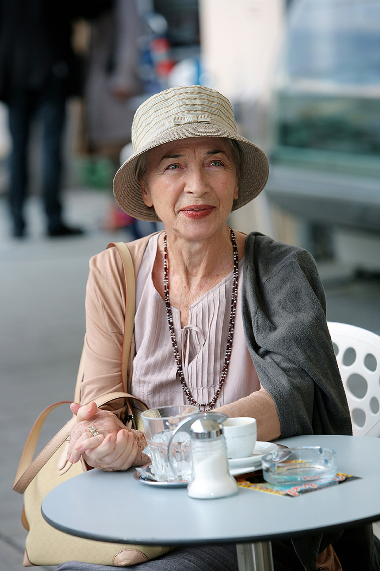 Christine Ostermayer sitzt im Freien an Kaffeehaustisch und lächelt.