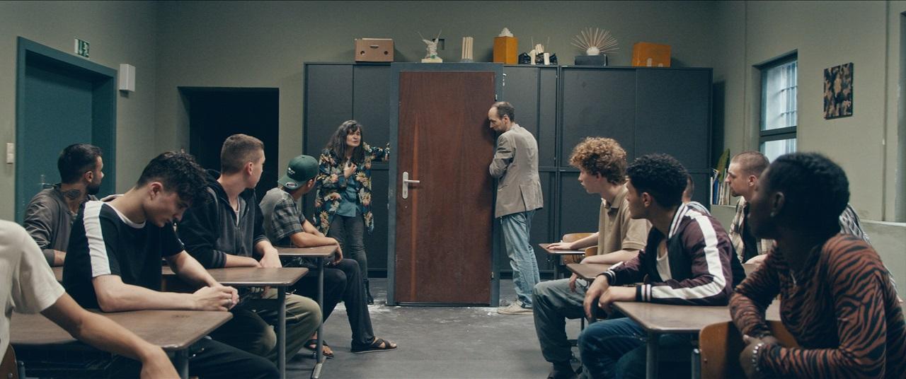 """Maria Hofstätter und Aleksandar Petrović in einem Klassenzimmer in einer Haftanstalt im Film """"Fuchs im Bau""""."""