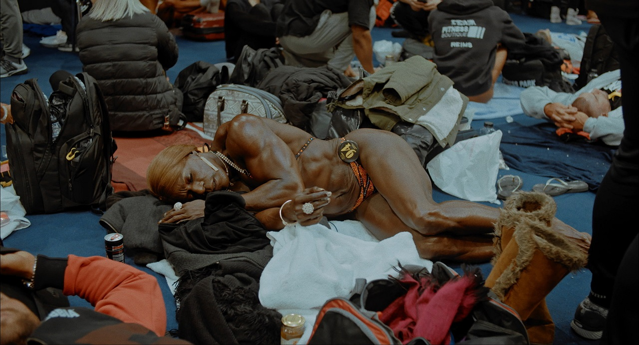 "Bodybuilderin Tischa Thomas ruht inmitten Wartender. Szene aus ""I Am The Tigress""."