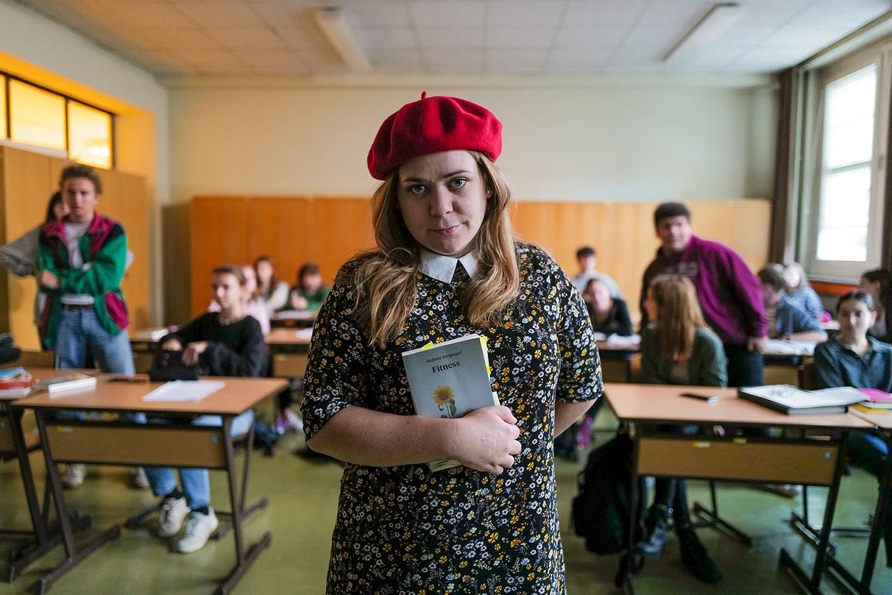 """Stefanie Sargnagel steht mit einem Buch in der Hand in einer Schulklasse. Szene aus dem Film """"Sargnagel""""."""
