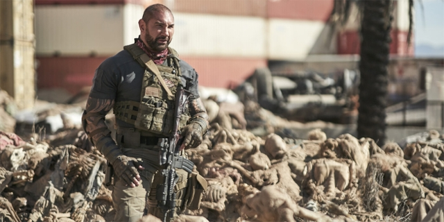 Mann mit Waffe inmitten eines Haufens menschlicher Überreste
