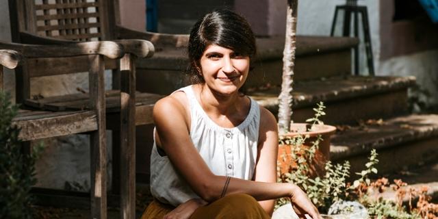 Autorin Shida Bazyar mit weißem, ärmellosem Top sitzt auf Stufen in einem Garten