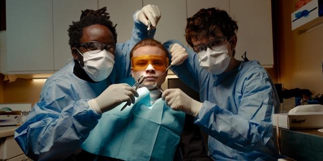 black midi, drei Bandmitglieder sind als Zahnärzte & Patient dargestellt