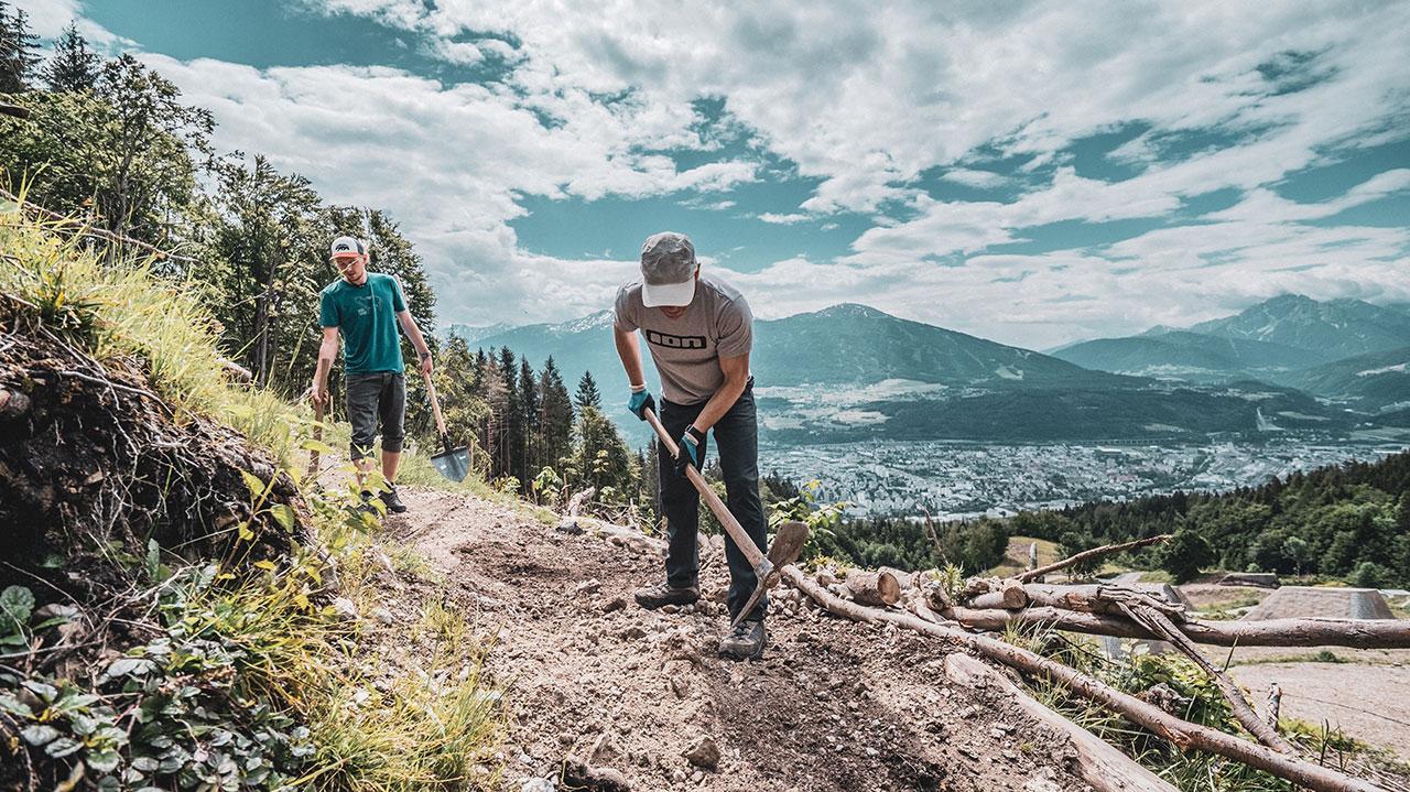 Zwei Personen graben einen Trail mit Hammer und Spitzhacke