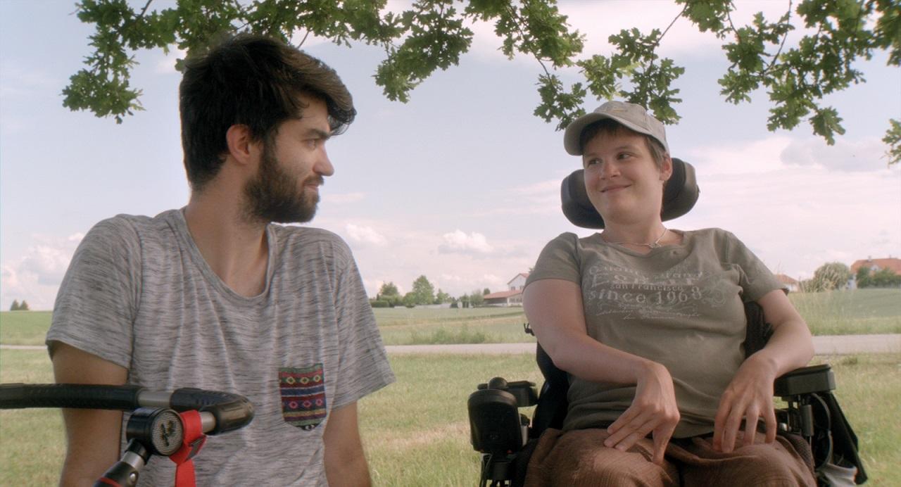 """Filmemacher und persönlicher Assistent Lukas Ladner und Eva-Maria sitzen im Freien. Szene aus der Doku """"Eva-Maria""""."""