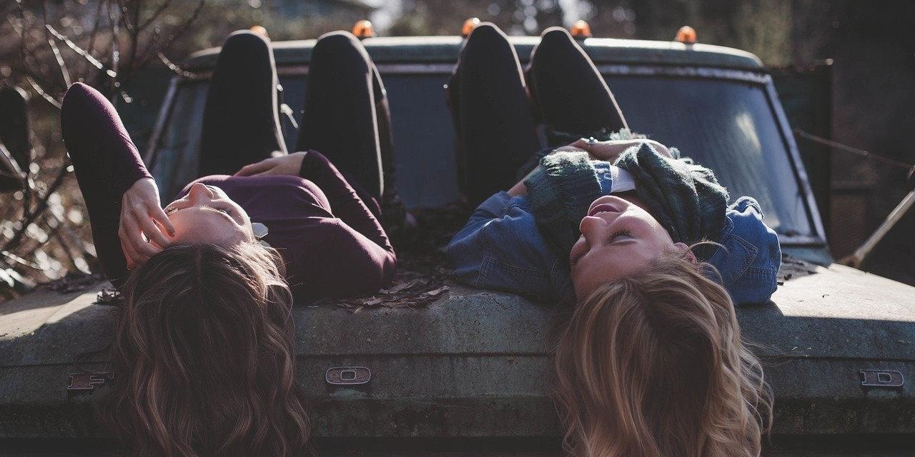 junge Frauen liegend auf Auto