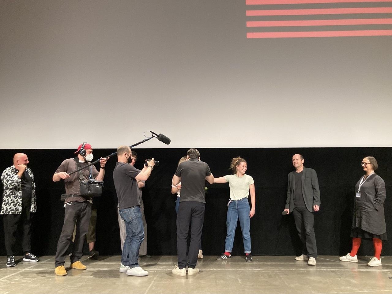 Sebastian Brauneis mit Team überraschen eine Schauspielerin auf der Diagonale 2021 mit einem Preis.