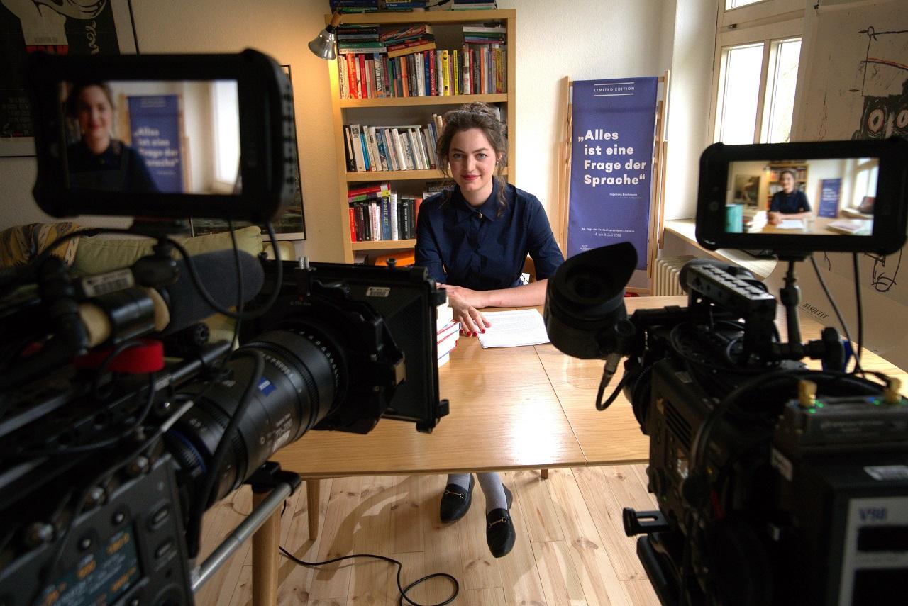 Dana Vowinckel sitzt an einem Schreibtisch und vor ihr stehen zwei Kameras.