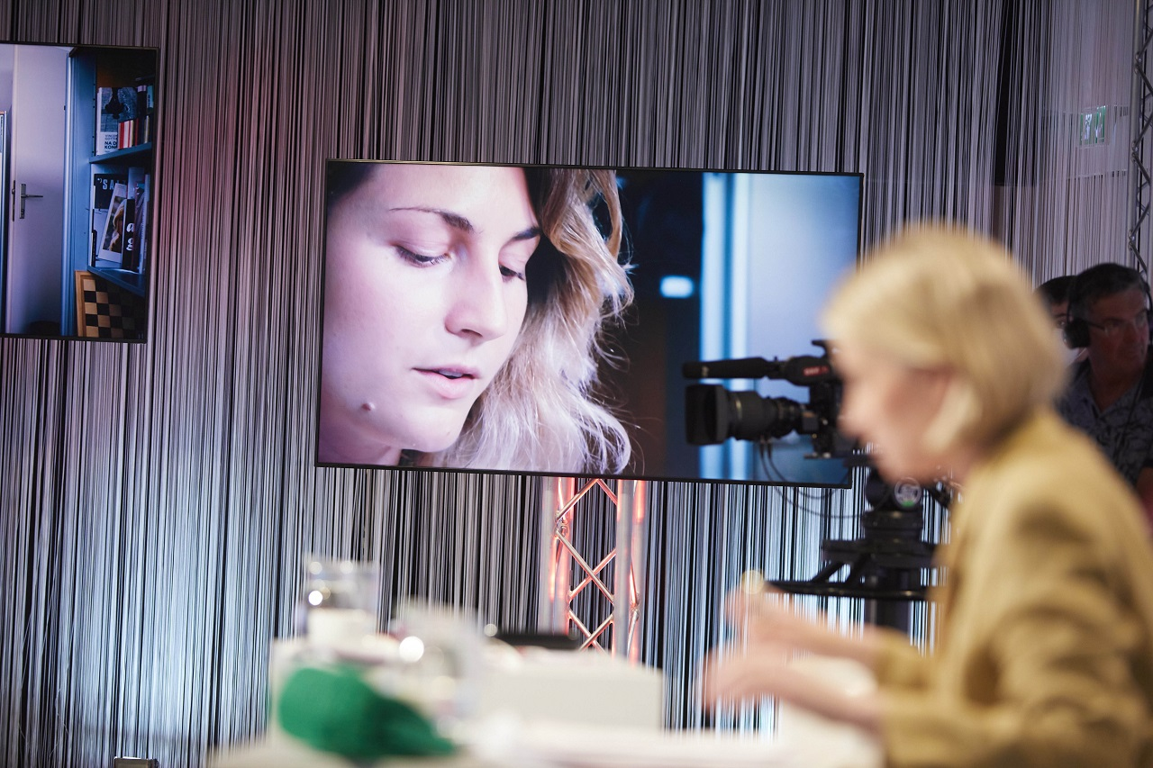 Verena Gotthardt bei ihrer Lesung auf einem Bildschirm und die Jurorin Mara Delius