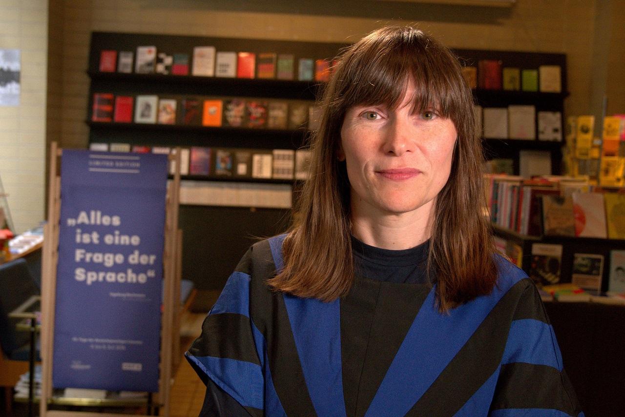 Autorin Heike Geißler sitzt an einem Tisch.